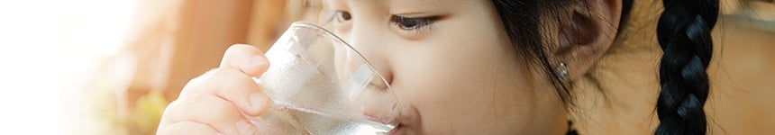 Young girl drinking water from glass