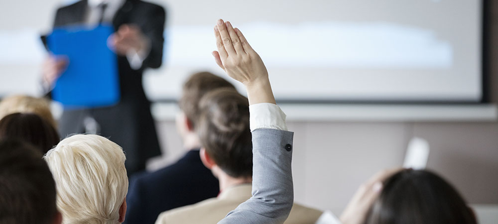image of person in meeting with a raised hand to ask a question