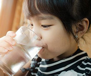 A child drinking a glass of water